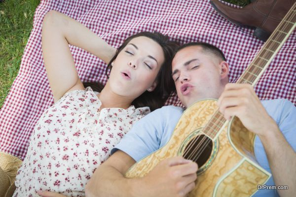 Happy Mixed Race Couple On Picnic Blanket at the Park Playing Guitar and Singing Songs.