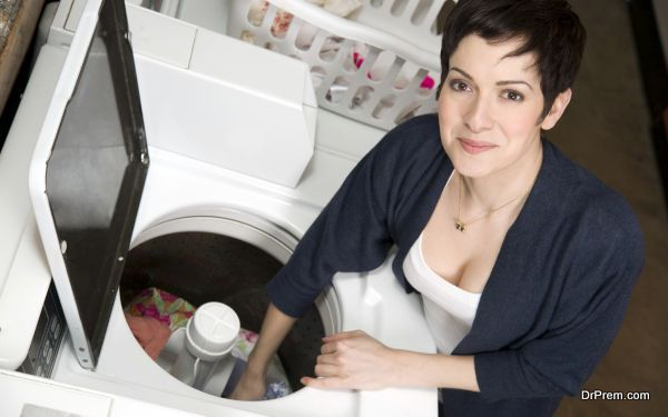 A woman pulls clothes from the washer at the laundromat