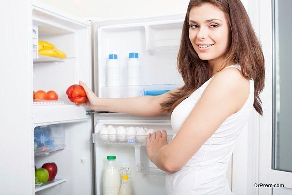 Woman taking pepper from fridge