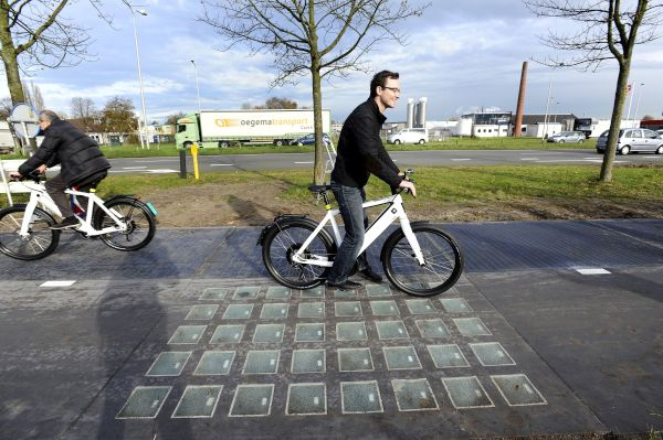 "Cyclists use the SolaRoad, the first road in the world made of solar panels, during the official opening in Krommenie on November 12, 2014. The Netherlands unveiled the world's first solar bike path, a revolutionary project to harvest the sun's energy that could eventually also be used on roads. The so-called ""SolaRoad"" bike path is made of concrete modules each measuring 2.5 by 3.5 metres (eight by 11 feet), embedded with solar panels covered in tempered glass.  AFP PHOTO/ANP/EVERT ELZINGA == NETHERLANDS OUT ==        (Photo credit should read EVERT ELZINGA/AFP/Getty Images)"