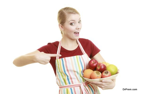 Diet and nutrition. Happy housewife or chef in striped kitchen apron offering healthy fruit isolated