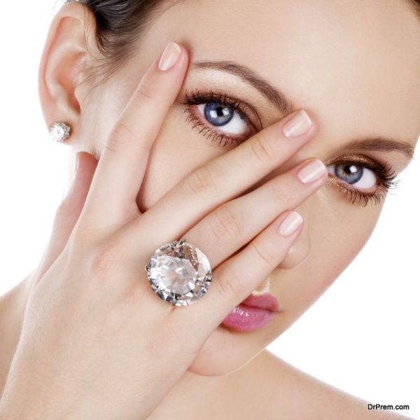 Woman peaking through her fingers to show a diamond ring