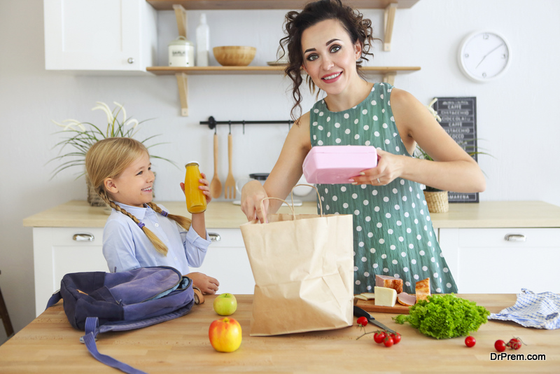 mom giving lunch to her child in a reusable container